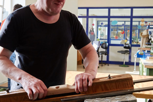 Mann bearbeitet Besenkopf im Schraubstock in der Werkstatt.