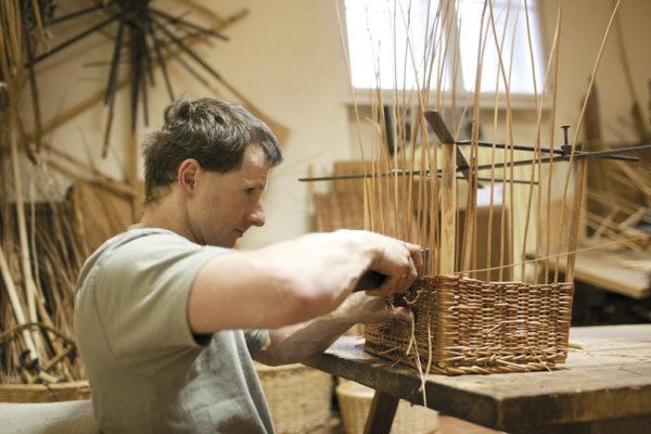 Mann in Werkstatt flechtet einen quadratischen Weidenkorb.
