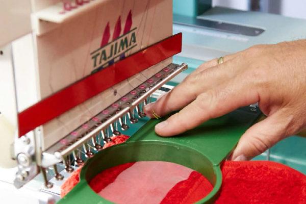 Männerhände halten eine Schablone über Stoff vor einer industriellen Nähmaschine