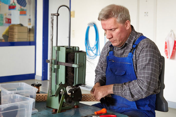 Besenherstellung: Mann in Arbeitsmontur verarbeitet ein Holzbesenbürstenstück an einer Fräse