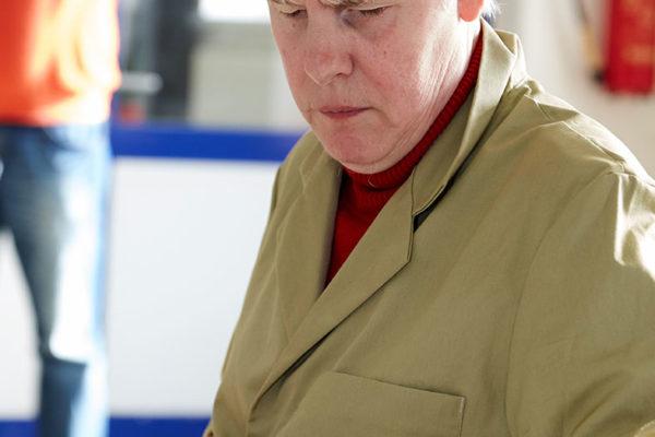 Abbildung einer blinden Frau an einer Werkbank.