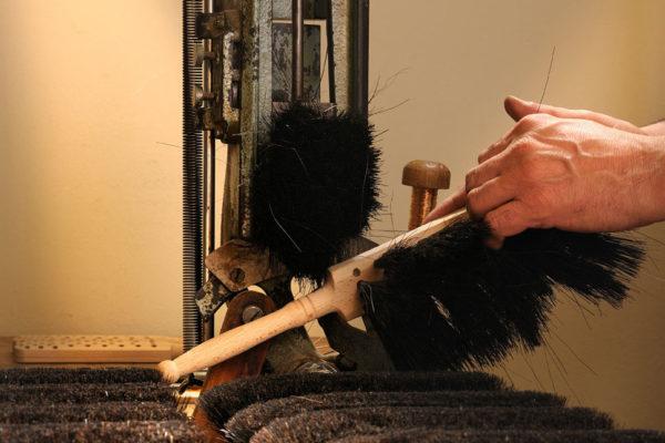 Männerhände fertigen Handfeger in der Bürstenzieherei. Mehrere gefertigte Exemplare liegen auf der Werkbank.