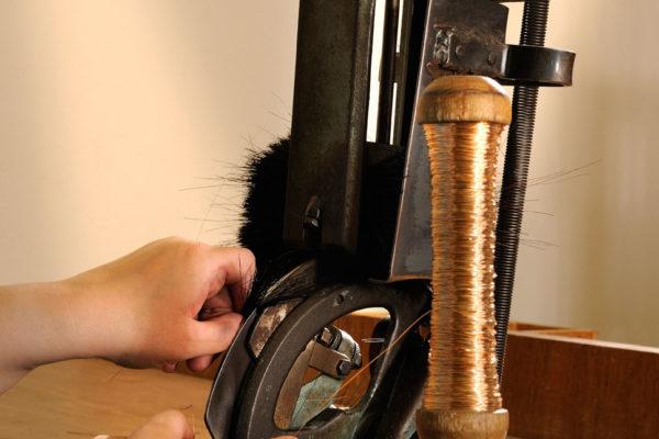Frauenhände an Bürstenziehmaschine ziehen Bürstenhaare in einen Handfeger.