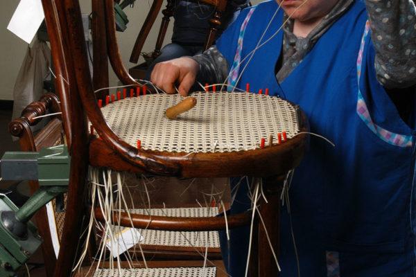 Frauen mit Arbeitskleidung in Werkstatt flechten Stuhlsitze.