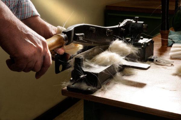 Mann an Werkbank schneidet Bürstenhaare mit Schneidemaschine.