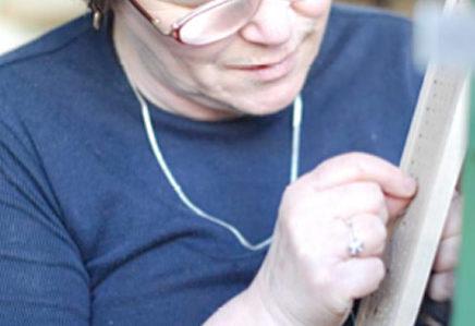 Sehbehinderte Frau mit Brille knüpft Bürstenhaare in einen Besenkopf.