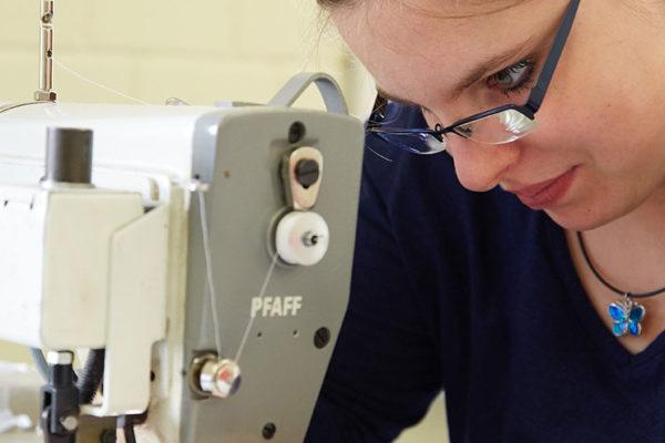 Näherin arbeitet an einer Nähmaschine