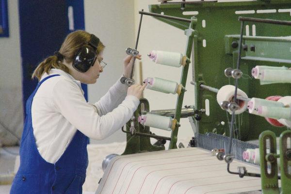 Weberei: Frau mit Gehöhrschutz in Arbeitskleidung richtet Fäden an einer industriellen Webmaschine ein